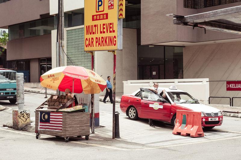APS-C DSLR Hawker Food Randmotiv Taxi Driver Building Exterior City Men Nklb Real People Security Guard Sign Street Scene Umbrella