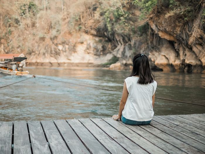 Rear view of woman sitting on wood by river