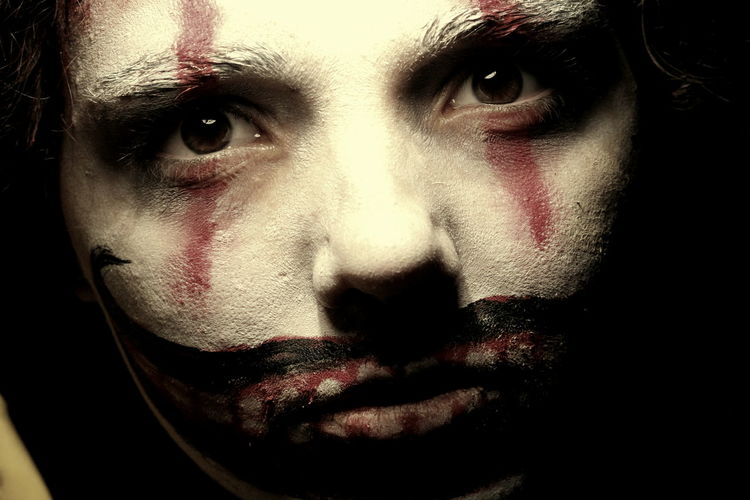 Close-up portrait of woman with spooky halloween make-up in dark