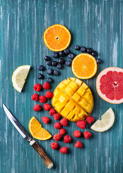 Slices of fresh fruits over metal blue background. Top view Bio Blueberry Citrus  Citrus Fruit Detox Food Fresh Fruit Grape Healthy Healthy Eating Lemon Mango Organic Raspberry