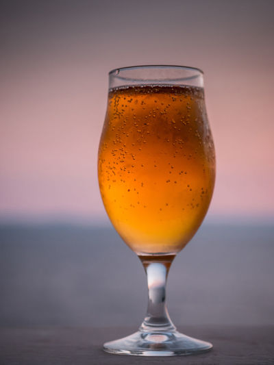 Close-Up Of Beer Glass Against Sea During Sunset