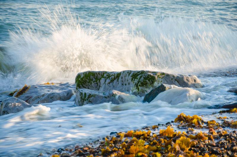 Scenic view of waves splashing on rocks at beach