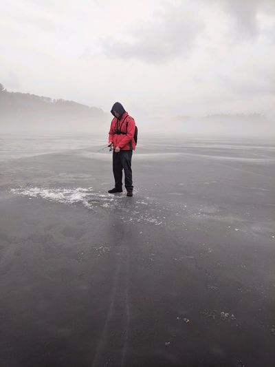 Man standing at frozen sea against sky