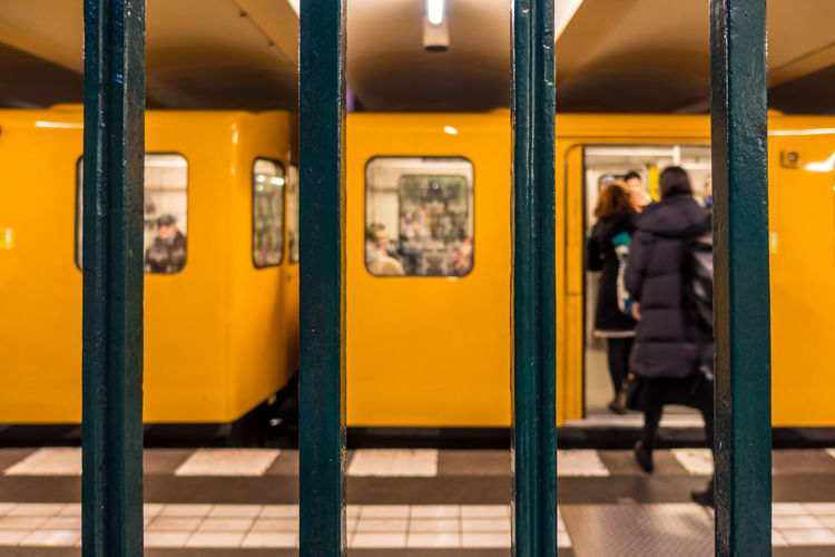 People Getting In Train Seen Through Subway Station