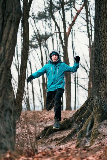 Low angle view of young man running in forest