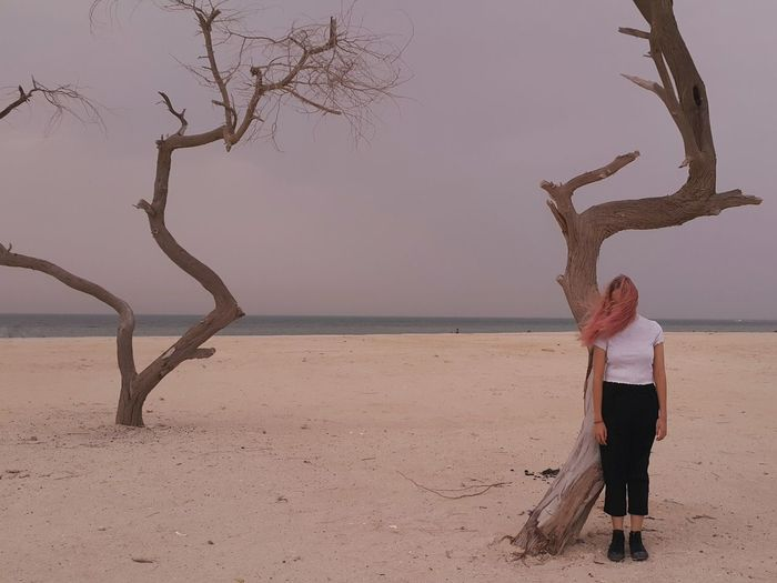 Full length of man standing on tree at beach