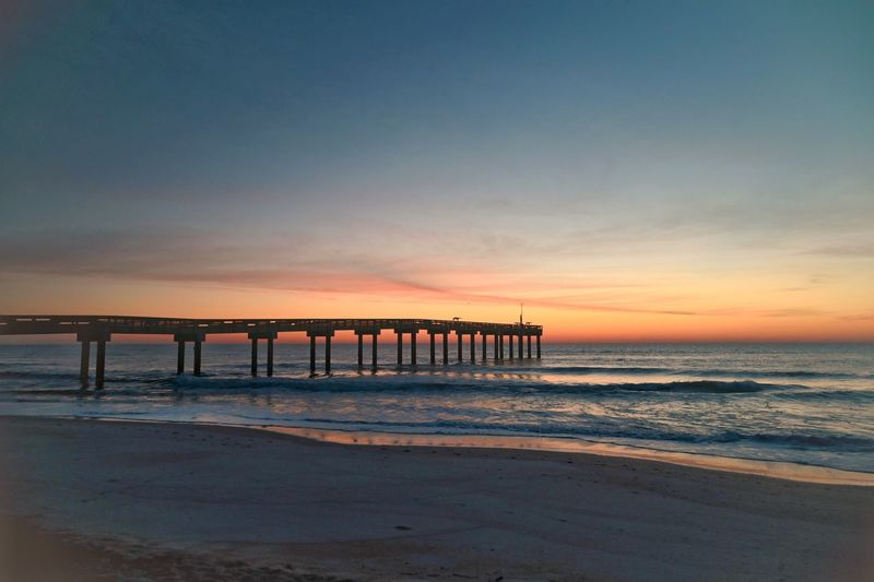Pier over sea against sky during sunset