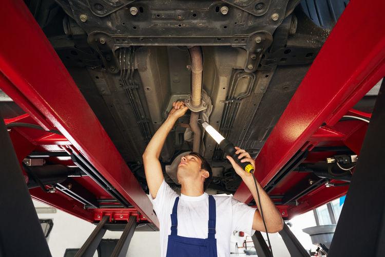 Low angle view of mechanic repairing car in garage