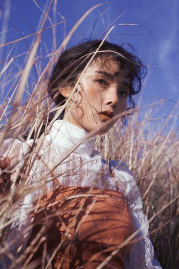 Portrait of woman looking away on field