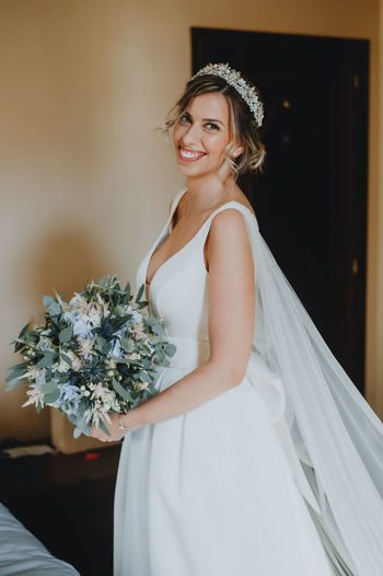 Portrait of smiling bride holding bouquet at home