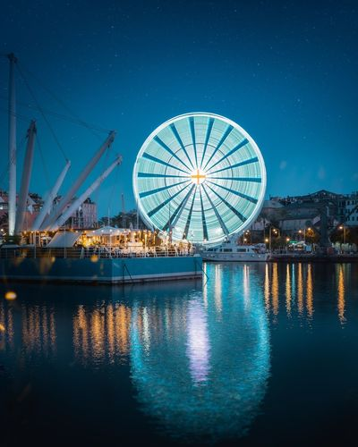 Reflection of illuminated ferris wheel in lake at night