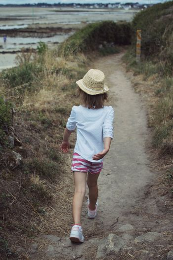 Rear view of girl walking on shoreline