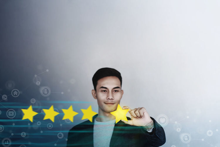 Customer Experience Concept. Young Businessman with Happy Face Showing his Five Star Services Rating Satisfaction. Happy Client's Feedback and Online Review. Surrounded by Network Icons One Person Portrait Looking At Camera Indoors  Front View Young Adult Holding Men Casual Clothing Young Men Yellow Lifestyles Studio Shot Males  Smiling Waist Up Standing Leisure Activity Hairstyle Customer Experiences Feedback Review Five Star Online  Client Happy Customer