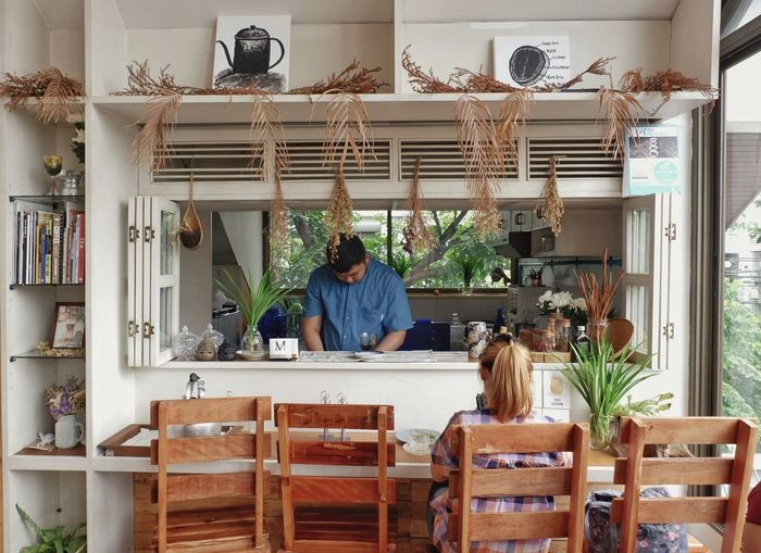 A woman sitting in front of barista waiting for her coffee in the cafe Real People Plant Occupation Lifestyles Day Front View One Man Only Potted Plant Indoors  Coffee Barista Cafe Chair Shelf Counter Wait Window Sunshine Dry Flower  Book Wood Vintage Cafehopping