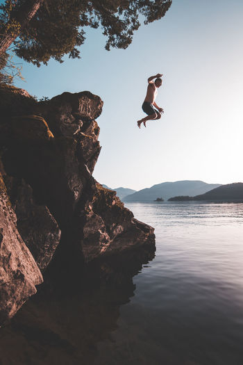 Shirtless Young Man Diving Into Sea Against Clear Sky