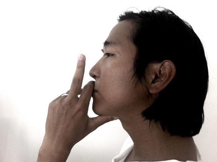 Profile view of young man showing middle finger against white background