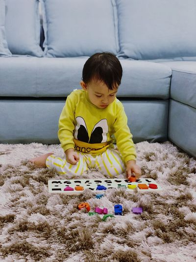 Baby boy playing with toys while sitting on rug at home