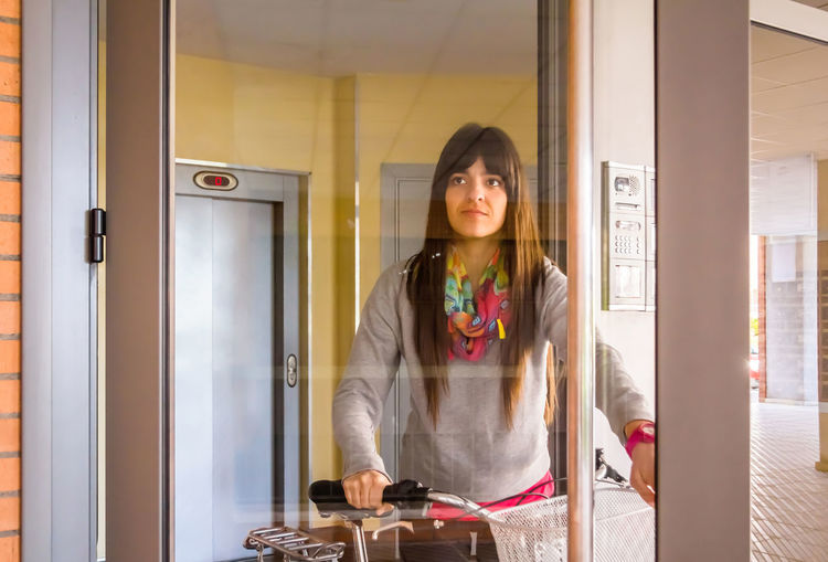 Woman with bicycle standing seen through glass door