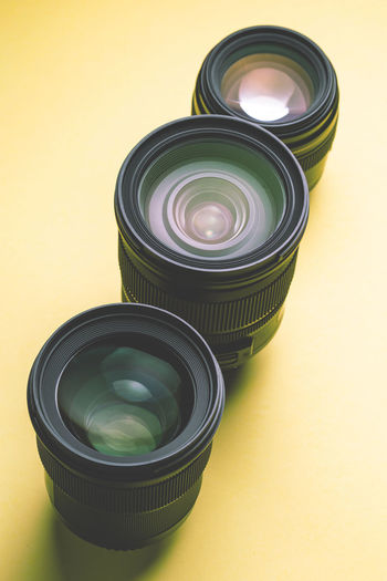 close up of dslr lenses on yellow background Still Life Indoors  Table No People High Angle View Container Colored Background Yellow Studio Shot Glass - Material Close-up Green Color Lid Group Of Objects Jar Yellow Background Medium Group Of Objects Circle Geometric Shape Photography Themes