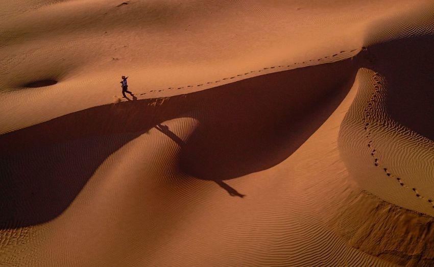High Angle View Of Man Walking On Sand Dune