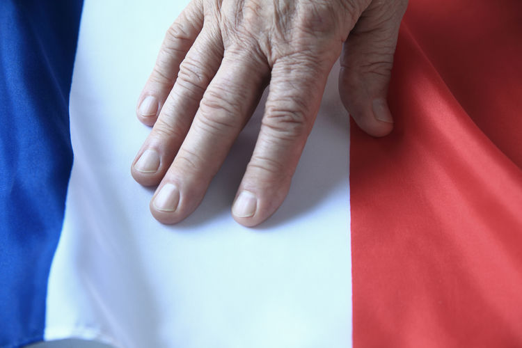 Cropped hand of person on french flag