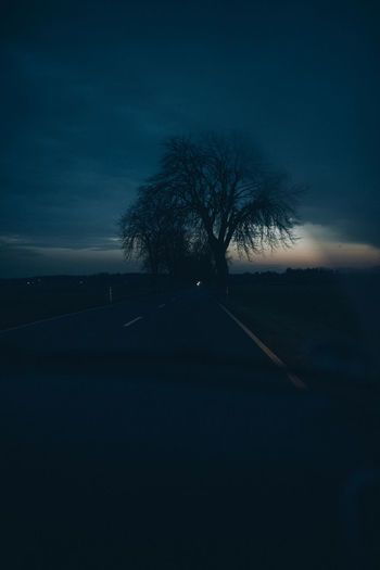 Silhouette bare tree by road against sky at dusk