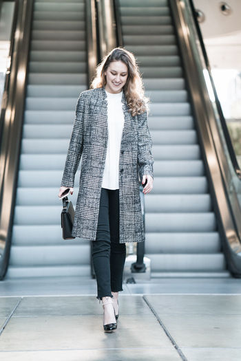Young beautiful blond happy woman businesswoman walking from escalator moving down lifestyle fashion One Person Front View Real People Architecture Young Adult Full Length Clothing Looking At Camera Standing Adult Lifestyles Women Beauty Portrait Indoors  Staircase Young Women Beautiful Woman Steps And Staircases Hairstyle Warm Clothing Businesswoman Walking Walk Travel