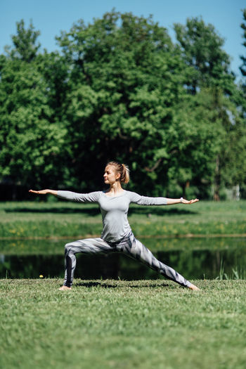 Full length of woman exercising on field by lake at park