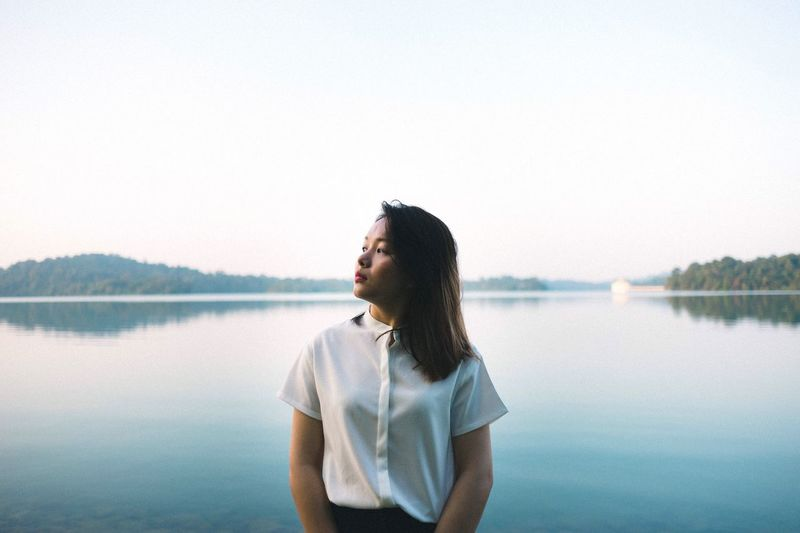6AMs Women Around The World Waist Up Real People Young Adult One Person Water Lifestyles Casual Clothing Lake Reflection Young Women Clear Sky Nature Leisure Activity Standing Scenics Day Tranquil Scene Beauty In Nature Outdoors Sky Portrait Singapore Long Goodbye