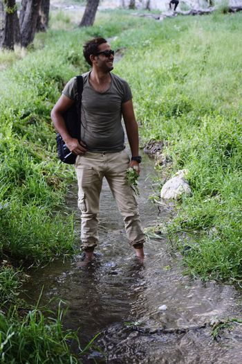 Young man with backpack standing in stream amidst plants
