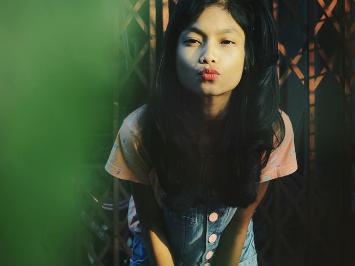 Portrait of girl puckering lips while standing outdoors