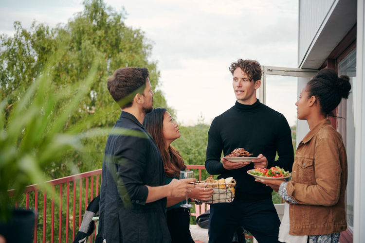 Group of people standing by food outdoors