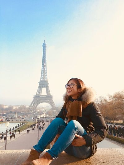 Smiling young woman sitting against eiffel tower in city