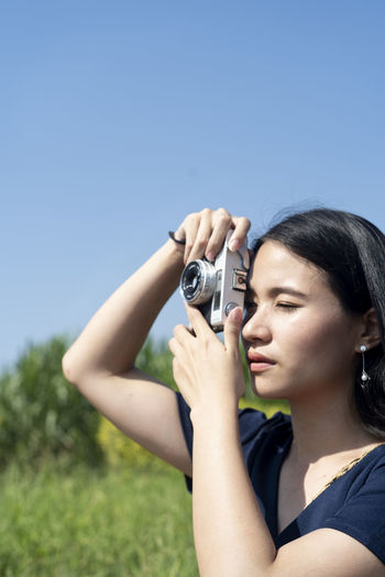 Midsection of woman photographing against clear sky