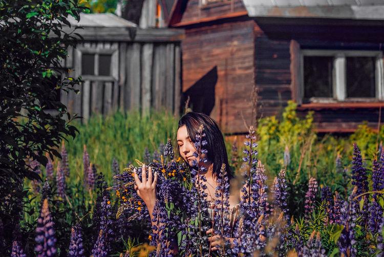 Full length of woman holding flowering plants