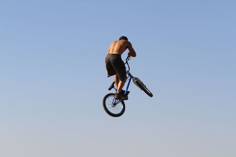Rear View Of Cyclist Performing Stunt In Mid-Air Against Clear Blue Sky