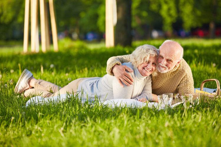 Portrait Of Senior Couple Lying On Grassy Field At Public Park