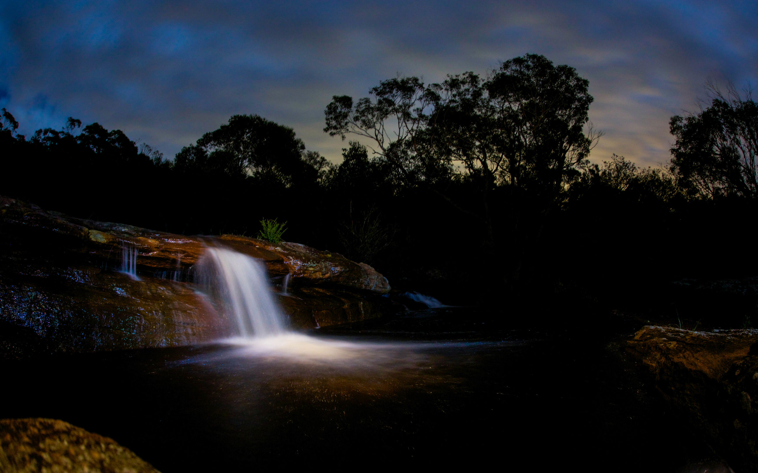 tree, water, long exposure, scenics, sky, beauty in nature, motion, nature, waterfall, flowing water, tranquil scene, tranquility, cloud - sky, idyllic, rock - object, flowing, outdoors, forest, silhouette, no people