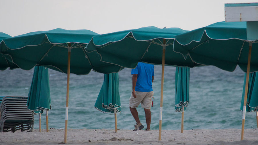 Rear view of man walking by parasols at beach