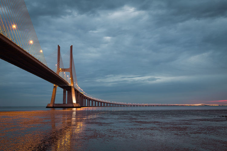 Bridge Over Sea Against Cloudy Sky At Dusk