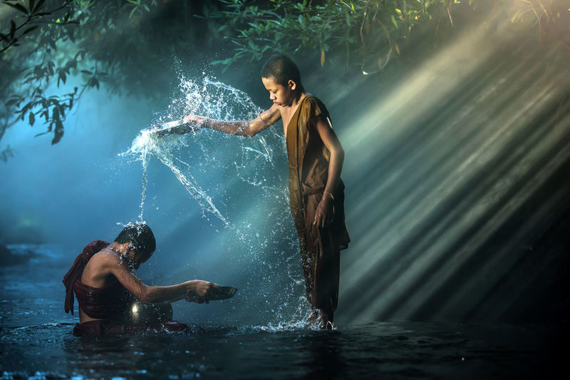 Boy Wearing Traditional Clothing While Pouring Water On Teenager In Lake At Forest