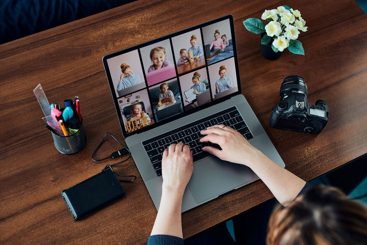 Female photographer working on photos on laptop and camera. woman editing retouching browsing photos