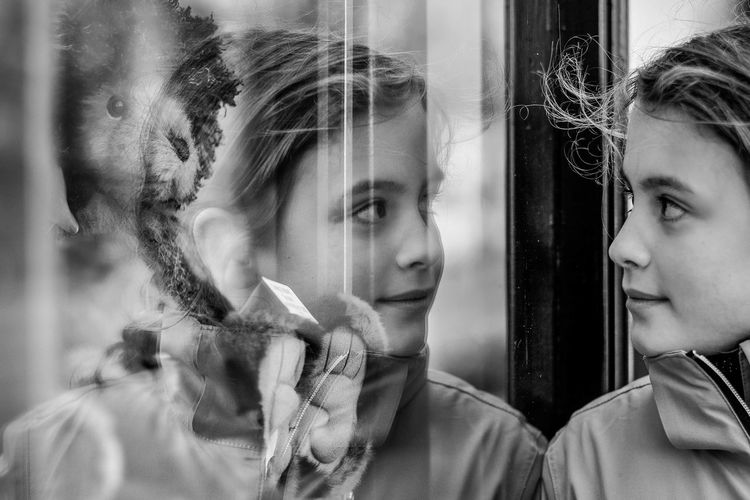 Close-up of girl reflecting on glass window