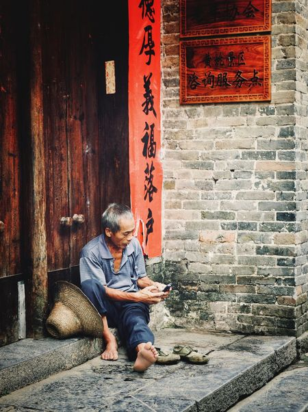 Modern old age Hezhou China People Lifestyle Real People Streetphotography One Person Sitting Full Length Lifestyles Real People Communication Casual Clothing Text Men Architecture Adult Day Built Structure Outdoors