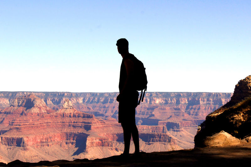 Silhouette of male hiker at edge of Grand Canyon. Grand Canyon Grand Canyon National Park Hiking Silhouette Arid Climate Beauty In Nature Canyon Clear Sky Cliff Full Length Geology Landscape Leisure Activity Nature One Person Outdoors Physical Geography Real People Rock - Object Rock Formation Scenics South Rim Tourism Travel Travel Destinations Summer Exploratorium