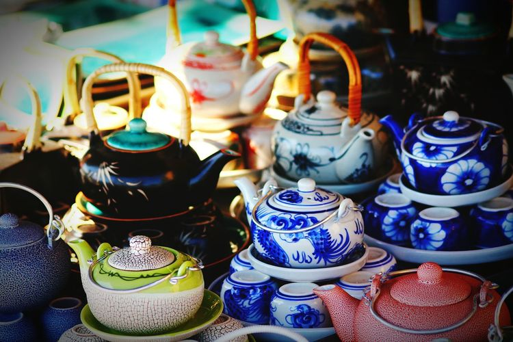 Close-up of colorful teapots for sale at street market