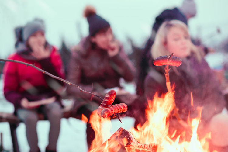 Family spending time together around campfire outdoors in the winter. People roasting sausages over the campfire using wooden sticks. People out of focus Campfire Flames Sausage Roasted Roasting Sticks Enjoyment Outdoors Picnic Gathering Together Family Food Preparing Winter Wintertime Wintery Snack People Blurred Lifestyles Leisure Fireplace Season  Happy