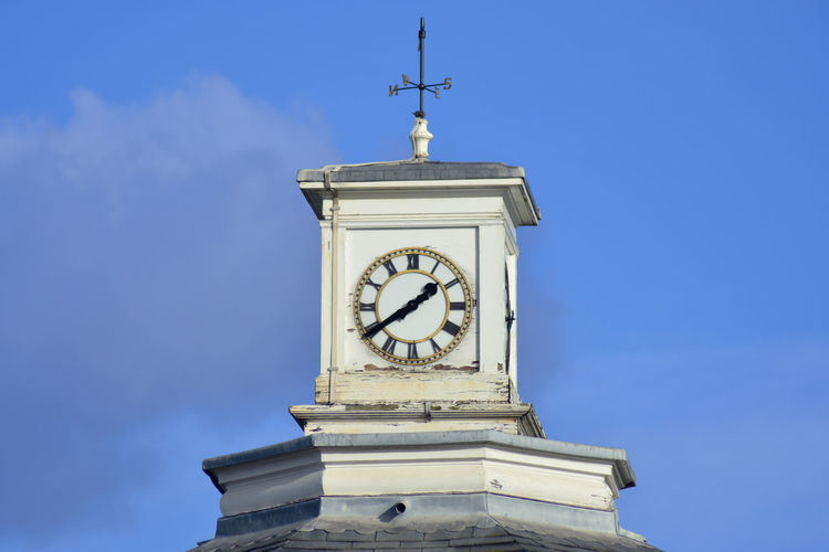 Low angle view of clock tower against blue sky