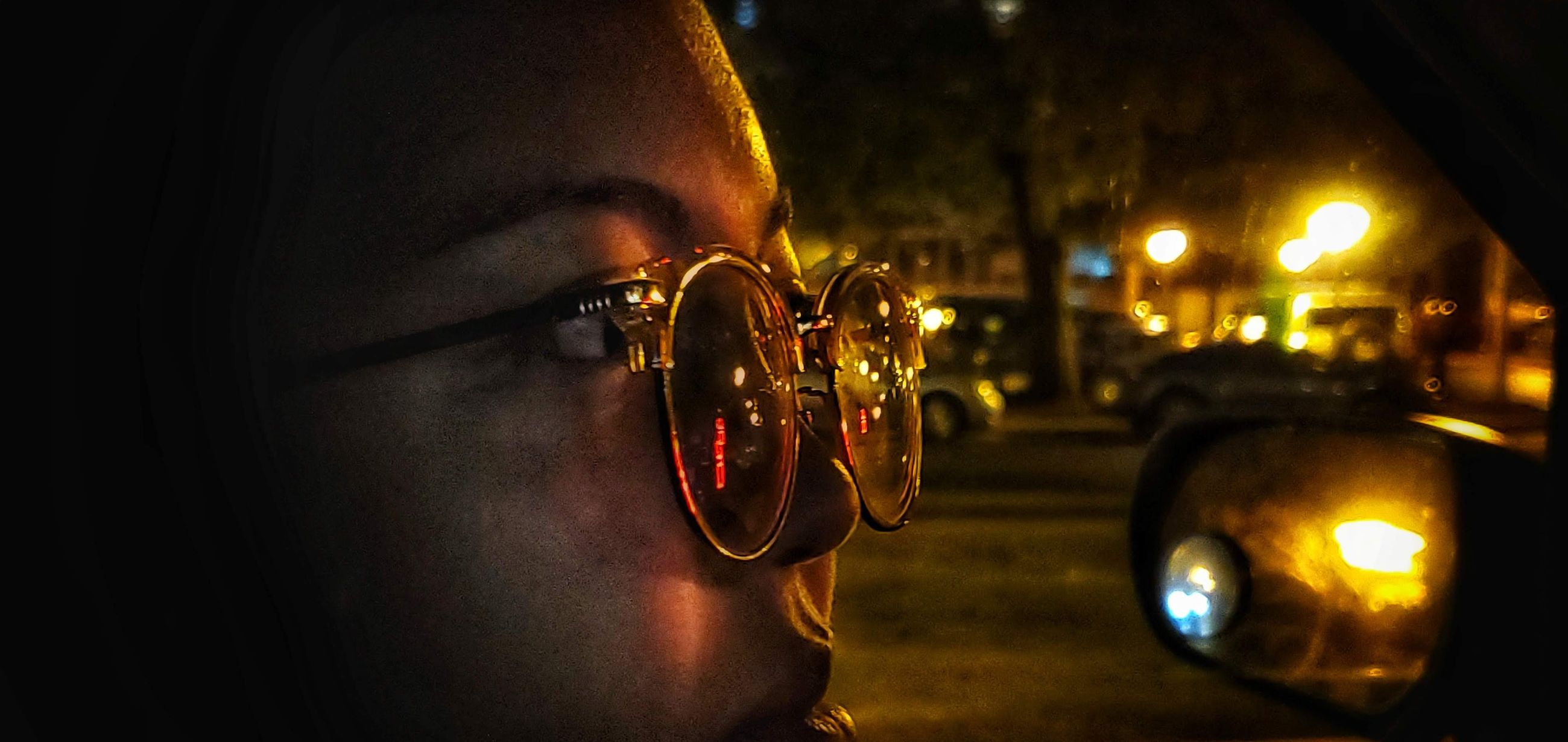 close-up, human body part, mode of transportation, focus on foreground, one person, illuminated, car, night, motor vehicle, land vehicle, transportation, real people, body part, outdoors, human hand, glasses, security, reflection, fashion
