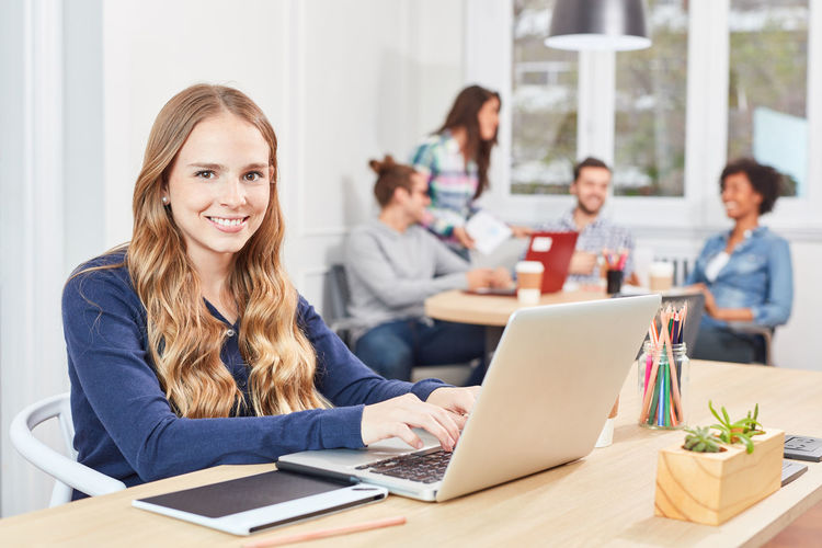 Portrait of cheerful businesswoman using laptop with colleagues in background at office